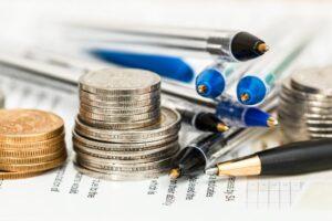 Cena urzędowa - czy się opłaca? Długopisy i akcesoria biurowe obok stosu monet
