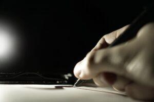 Dłoń z długopisem składa podpis na umowie, a nie ma uprawnień do tego, sfałszowany podpis