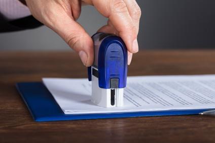 mężczyzna przykładający pieczątkę do dokumentu